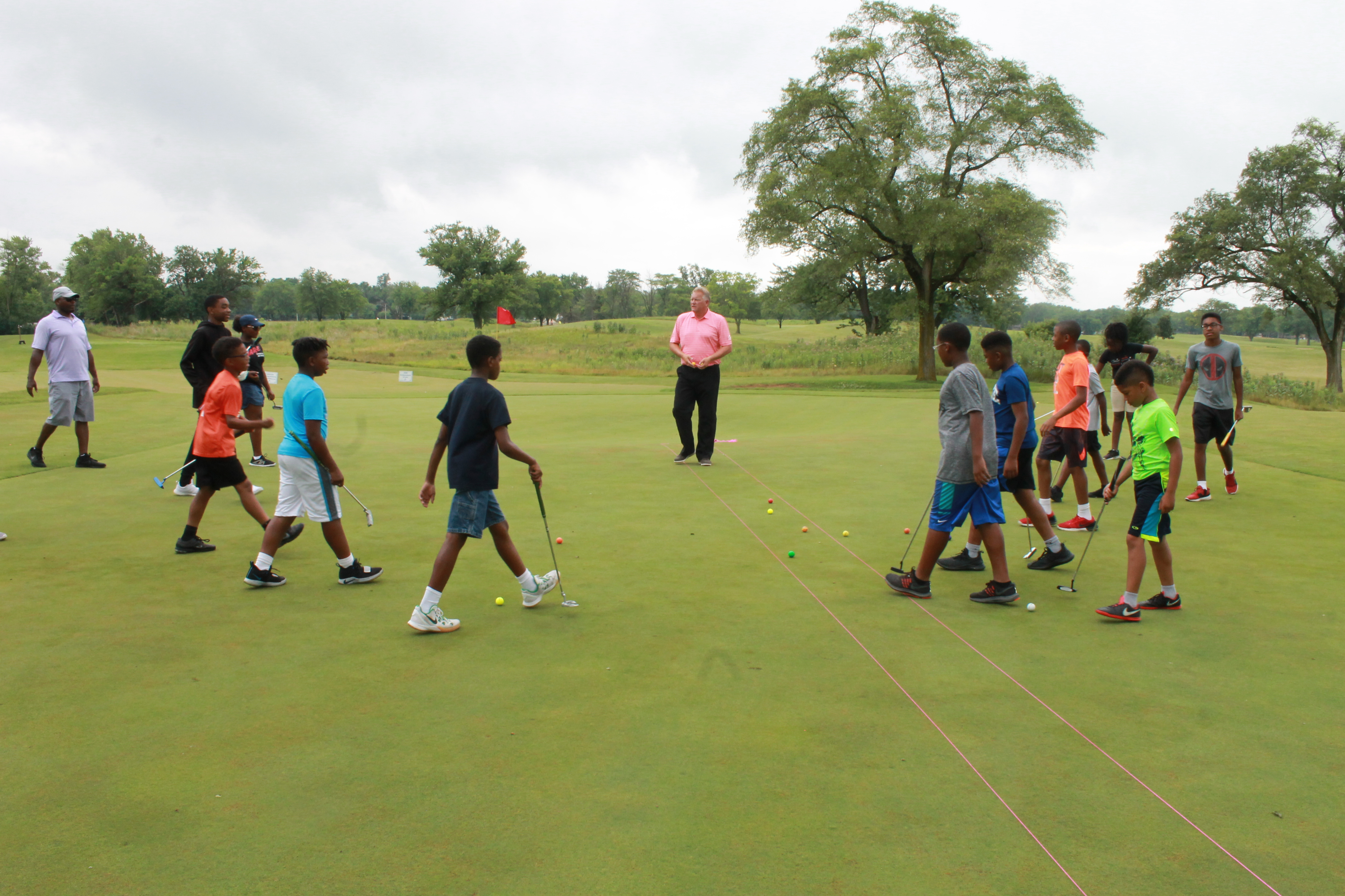 Jr. golfers gettting a lesson from Coyote Run's golf pro.
