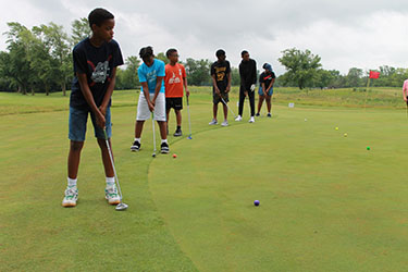 Jr. golfers practicing putting.