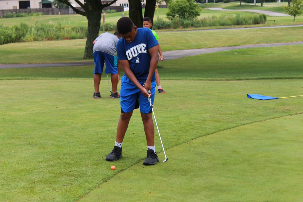Young golfers learning how to correctly putt at camp.