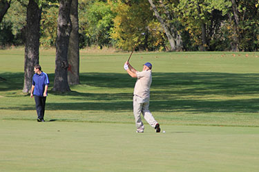 golfer hitting a perfect shot from the fairway.